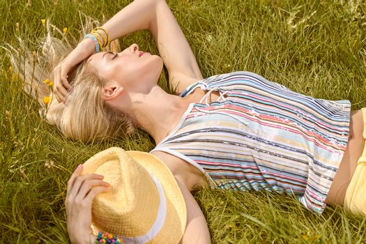 Beauty playful woman relax in summer garden dreaming on grass, people, outdoors. Attractive happy blonde girl enjoying nature, harmony on meadow, with hat, lifestyle. Sunny, forest, flowers, copyspace