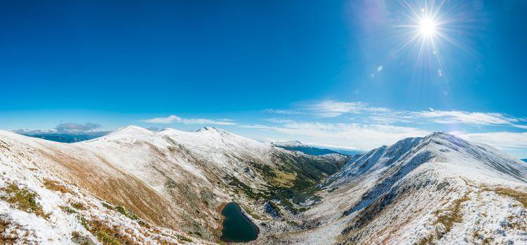 Panorama on beautiful mountain landscape with blue lake and shining sun