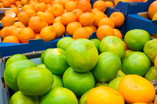 Pile of fresh green pamelos and oranges in the crates at market