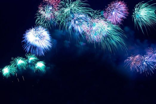 Colorful blue holiday fireworks on the black sky background