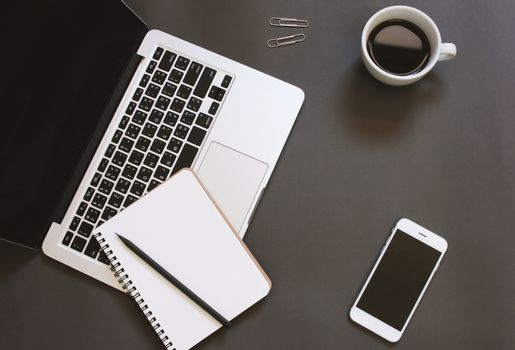 Creative flat lay design of workspace desk with laptop, notebook, smartphone and coffee with copy space background