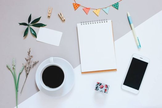 Creative flat lay design of cute workspace desk with notebook, coffee, smartphone and decorated cute craft with copy space background, minimal style