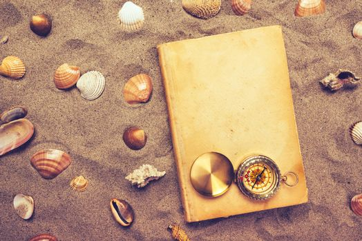 Vintage book and compass on sandy beach