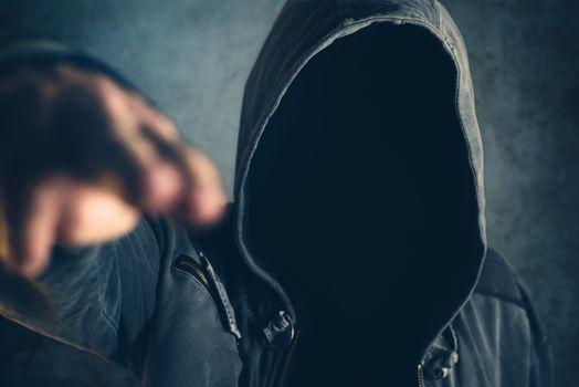 Hooded criminal gesturing gun shooting with fingers