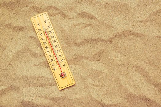 Record high temperatures, thermometer on warm desert sand
