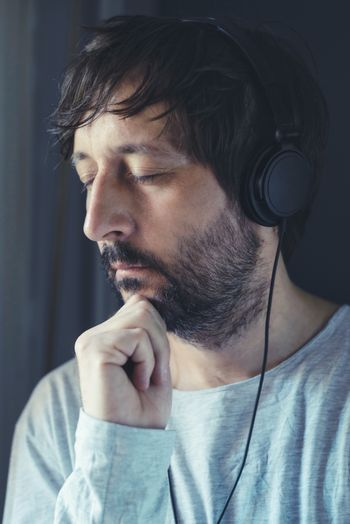 Man listening to music on headphones with eyes closed