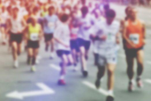Blur image of people running a marathon race through city