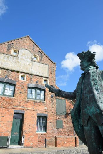 Statue of George Vancover Kings Lynn Norfolk with warehouse in background
