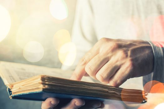 Man reading old book with torn pages