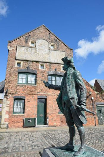 Statue of Maritime figure in front of Warehouse