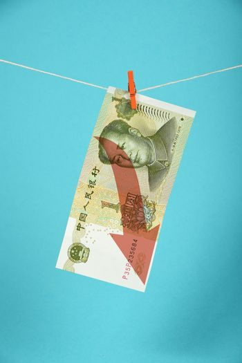 Chinese yuan decline illustrated over blue