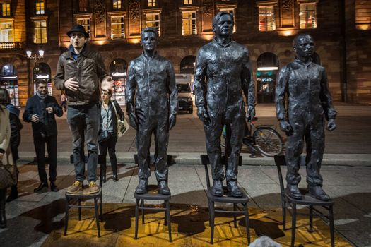 FRANCE, Strasbourg: Antoine Deltour stands on live size bronze sculpture Anything to say? of Italian artist Davide Dormino, portraying (2nd L-R) former National Security Agency (NSA) contractor and whistleblower Edward Snowden, WikiLeaks founder Julian Assange and former US soldier Chelsea Manning convicted of violations of the Espionage Act, in Strasbourg on November 17, 2015. The sculpture aims to be an interactive public art project for the freedom of speech. He and another former employees of accountancy giant PwC go on trial in Luxembourg on April 26, 2016 along with a French journalist, accused of leaking details of corporate tax deals that have fueled global demands for reform.