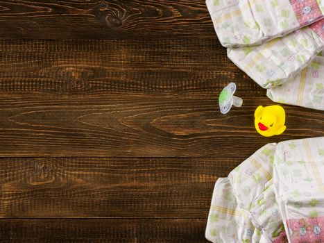 Japanese disposable diapers and dummy and rubber duckling on dark wooden background with copy-space. Flat lay