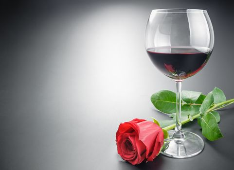 Glass of wine and rose flower
