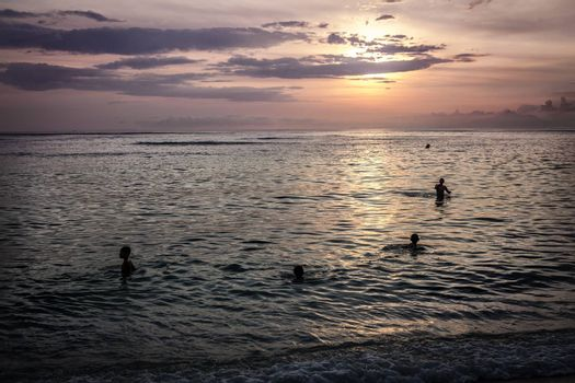 Children swim in the ocean evening sunset at Bali Indonesia