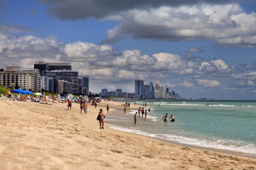 Miami Beach, USA - May 5, 2013: Scene of the crowded beach. People having fun, sunbathing and swimming in the shallow water. Skyline in the back.