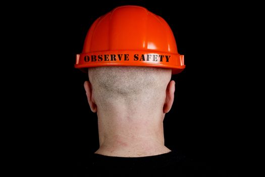 Construction worker in hard hat with an inscription observe safe