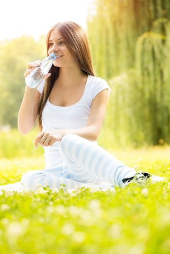 Smiling young woman drinks water from a bottle and enjoying in the nature.