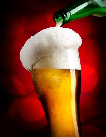 Pouring beer on red background