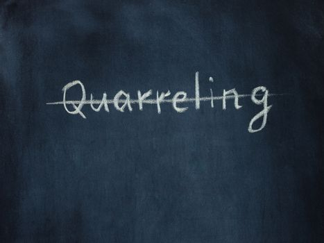 crossed out the word Quarreling on black chalkboard