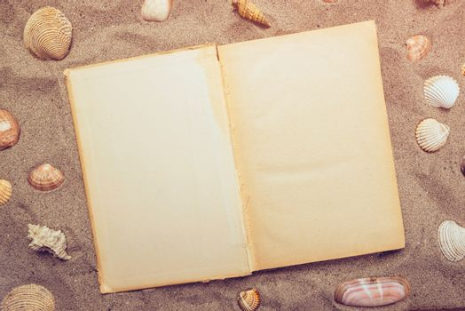 Top view of open book on sandy beach