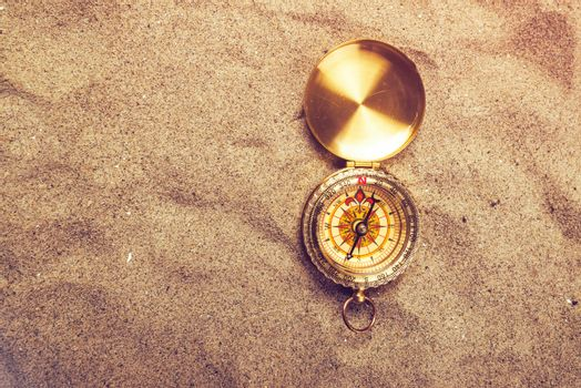 Top view of vintage compass on sandy beach