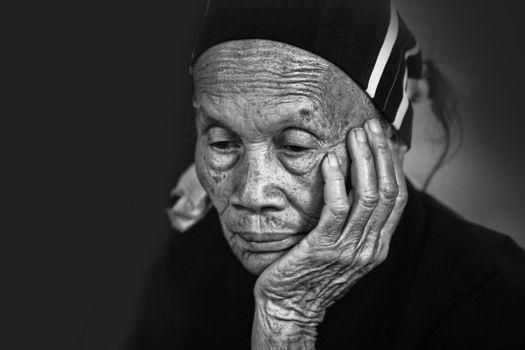 Hainan, China - April 7, 2012: Senior chanees woman with a worried expression face. China, Hainan - Li and Miao Village
