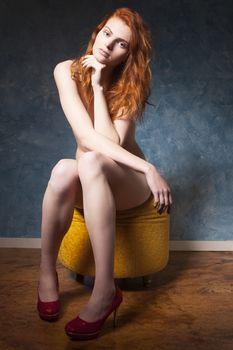 nude redhead sitting on a blue wall