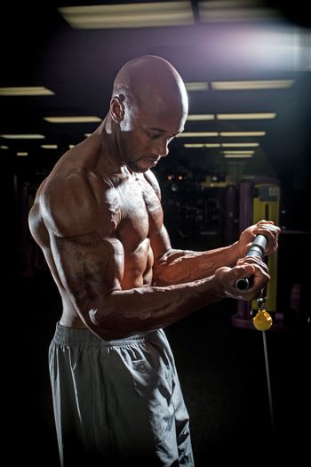 Body builder working out at the gym doing exercises on the cable machine under dramatic lighting.