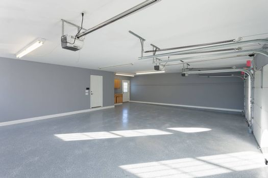 Beautiful brand new three car garage interior with finished floors and work space.
