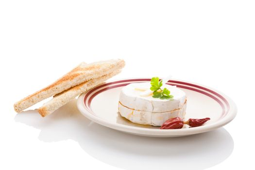 Delicious marinated camembert cheese on plate isolated on white background. Traditional czech cheese eating.