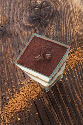 Tiramisu dessert with coffee beans and instant coffee on wooden textured table. Traditional tiramisu dessert, rustic, country style.