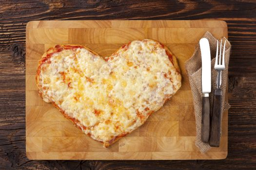 Culinary pizza eating. Pizza in heart shape on wooden table, top view. Culinary pizza eating. I love pizza.