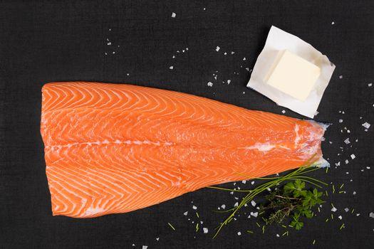 Fresh raw salmon background. Salmon steak with fresh herbs on black background, flat lay.