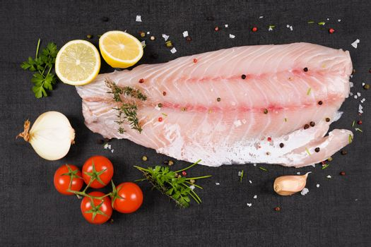 Luxurious perch fillet on black background, top view. Culinary fish eating.