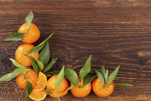 Fresh ripe mandarines with green leaves and copy space on wooden background. Organic fresh mandarines, healthy fruit eating.