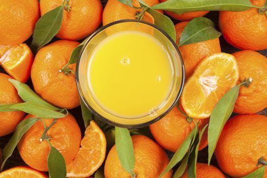 Fresh ripe mandarines with green leaves and orange juice seamless backdrop, flat lay, top view. Organic fresh mandarines, healthy fruit eating.
