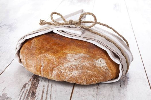 Delicious round bread loaf on white wooden table. Culinary bread eating.