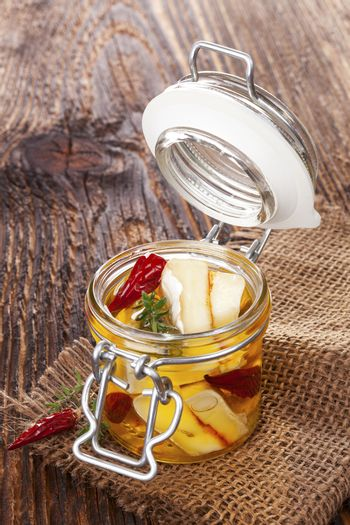 Marinated cheese in glass jar on brown wooden background. Culinary marinated cheese, rustic styles.