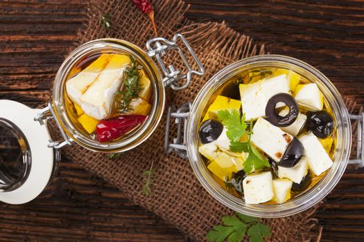 Marinated camembert and greek feat cheese in oil in glass jar on wooden table. Traditional culinary cheese eating.
