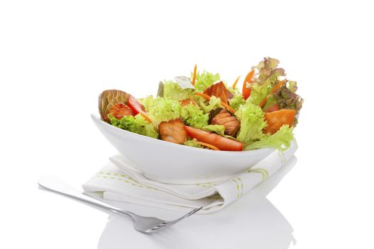 Fresh vegetable salad with roasted salmon pieces. Delicious healthy salad eating.