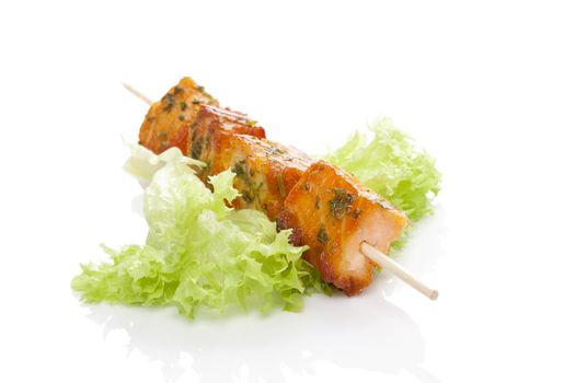 Salmon kebab. Salmon pieces on wooden skewer on green salad isolated on white background. Culinary salmon eating.