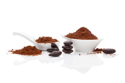 Cocoa beans and cocoa powder in white bowl and white spoon on white background. Healthy superfood.