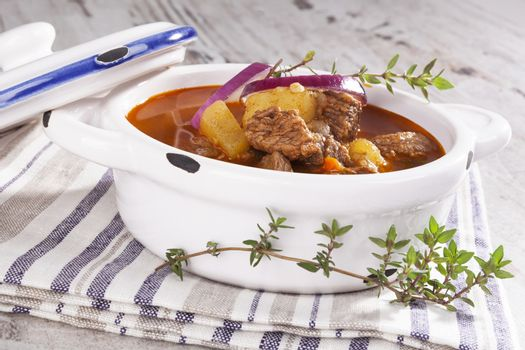 Delicious goulash soup in white pot on white wooden background. Culinary traditional goulash eating.