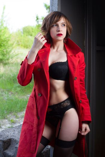 Attractive woman alluring in lingerie and coat.