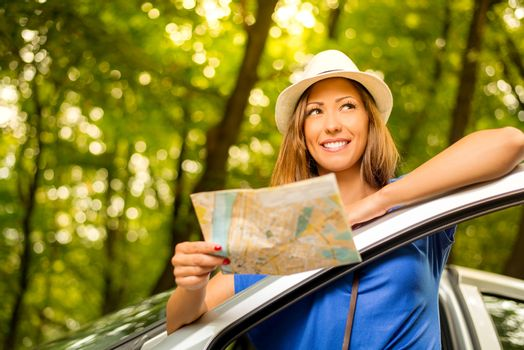Young beautiful woman standing leaning at car in the forest, holding map and looking away.