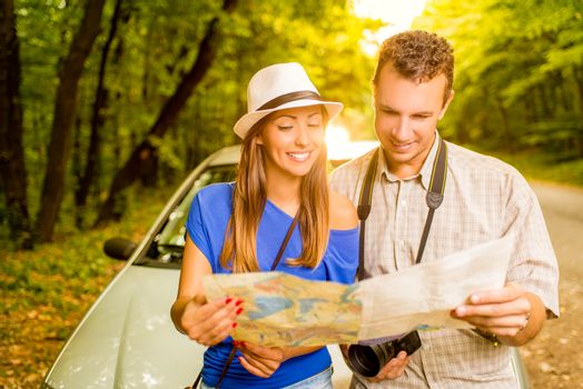 Young travelers standing before a car in the forest, holding map and searching next destination.