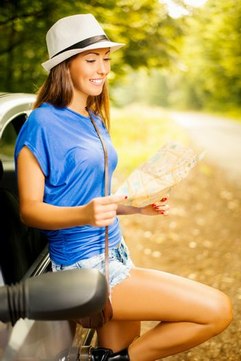 Young beautiful woman standing leaning at car in the forest and looking a map.