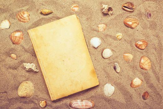 Vintage book and sea shells on sandy beach