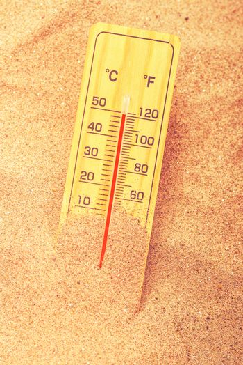 Thermometer on extreme warm desert sand